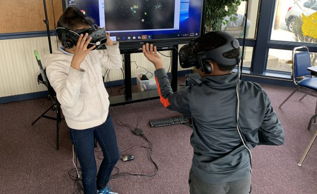 Students interact with virtual reality headsets